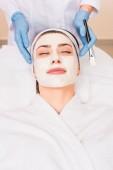 Kosmetikerin steht neben Frau mit geschlossenen Augen und Kosmetikmaske im Schönheitssalon