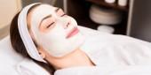 Frau im weißen Bademantel mit angewandter Gesichtsmaske liegend lächelnd im Schönheitssalon