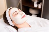 Frau im weißen Bademantel mit aufgesetzter Gesichtsmaske, lächelnd und geschlossenen Augen im Schönheitssalon