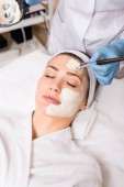 Fotografie Kosmetikerin trägt im Schönheitssalon Kosmetikmaske auf Gesicht der Frau mit Kosmetikpinsel und Haltegefäß auf