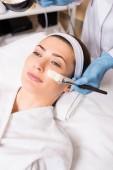 Kosmetikerin beginnt Kosmetikmaske mit Kosmetikpinsel auf Gesicht von Frau im Schönheitssalon aufzutragen
