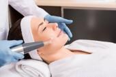 Fotografia estetista facendo darsonvalization sulla guancia di donna al salone di bellezza