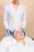Fotografia estetista che fa darsonvalization con attrezzature alla donna sul volto al salone di bellezza