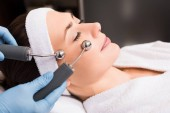 Photo beautician doing lifting massage on woman face at beauty salon