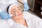 Fotografia massaggio che fa cosmetologo con attrezzature sul fronte della donna al salone di bellezza