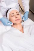 Fotografia estetista facendo massaggi con apparecchiature a donna sul volto al salone di bellezza