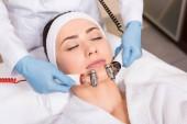 massaggio del viso che fa estetista con attrezzature di donna al salone di bellezza