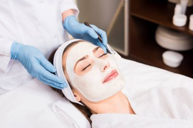 beautician standing and holding cosmetic brush near woman with cosmetic mask on face at beauty salon