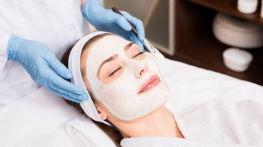beautician standing near woman with cosmetic mask on face and holding cosmetic brush at beauty salon