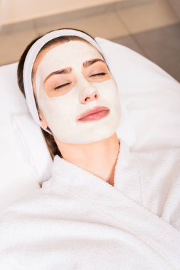 woman lying in white bathrobe with applied facial mask and closed eyes at beauty salon