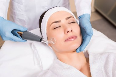 beautician doing darsonvalization with equipment to woman on cheek at beauty salon
