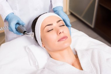 beatician holding darsonvalization equipment near woman face at beauty salon