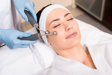 woman lying wile beautician doing lifting massage on face with equipment at beauty salon
