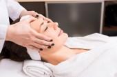 Fotografie kosmetička dávat masáž ruční obličeje ženy v beauty salonu