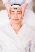 Fotografia cosmetologo che fa massaggio manuale viso alla donna che si trova sul accappatoio e infilo al salone di bellezza