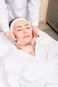 Fotografia cosmetologo facendo massaggi manuali sul fronte della donna al salone di bellezza