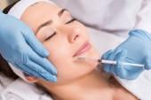 cosmetologo che fa iniezione sul volto di donna al salone di bellezza