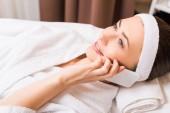 Fotografie atraktivní žena ležící v bílém županu a mluví na smartphone v beauty salonu