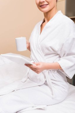 cropped view of woman sitting, holding cup and digital tablet at beauty salon
