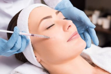 beautician making injection face attractive woman at beauty salon
