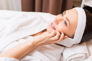 attractive woman lying in white bathrobe and talking on smartphone at beauty salon