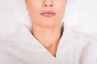 cropped view of woman lying in white bathrobe at beauty salon