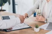 cropped view of businesswoman shaking hands with man and holding cash at workplace, compensation concept