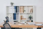 tabulka v úřadu s notebook, dokumenty, židle a knihovna fo složek na pozadí