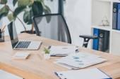 Selektivní fokus tabulky s notebookem, dokumenty, židle v kanceláři