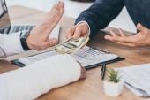 oříznutý pohled pracovníka odmítnutí peníze dávat podnikatel v modré bundě u stolu v kanceláři, kompenzace koncepce