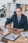 uomo daffari in giacca blu che si siede al tavolo e rifiutando busta dando da donna in ufficio, concetto di compensazione