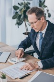 Fotografie middle aged businessman sitting at table, reading document and counting with calculator in office, compensation concept