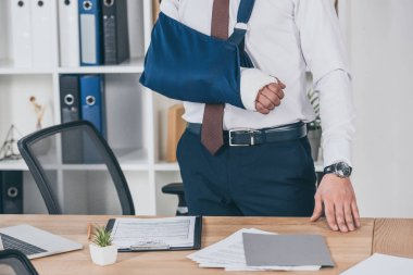 cropped view of worker with broken arm in bandage standing near table in office, compensation concept
