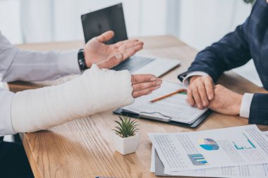 cropped view of worker with broken arm siting at table with documents opposite businessman in office, compensation concept