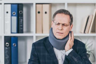man in neck brace sitting, feeling pain and holding neck in office, compensation concept