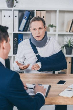 middle aged worker in neck brace with broken arm sitting at table and talking to opposite businessman in office, compensation concept
