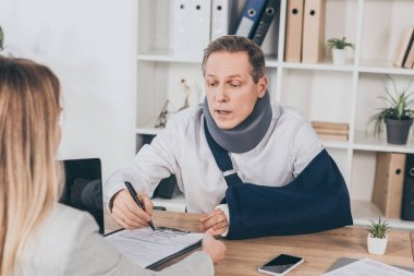 worker in neck brace and arm bandage at table pointing with pen in document while woman sitting opposite in office, compensation concept
