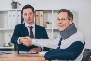businessman shaking hands with worker in neck brace and arm bandage over table in office, compensation concept
