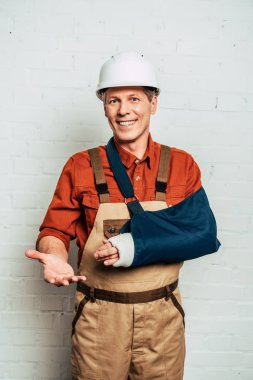 repairman with arm bandage standing on white textured background