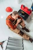 Fényképek felülnézet szerelőt ül a földön a sérült térd körüli, az irodai berendezések