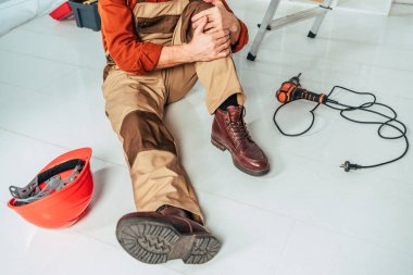 cropped view of repairman sitting on floor and holding injured knee in office
