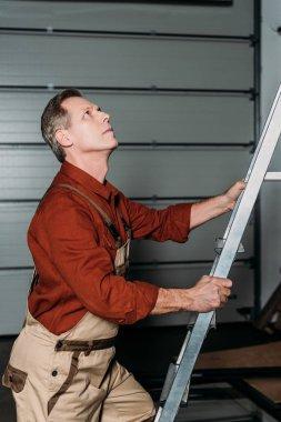 repairman in orange uniform climbing on ladder in garage