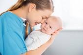 boční pohled šťastné mladé matky nesou a objímání rozkošné dítě při pohledu na fotoaparát v nemocničním pokoji