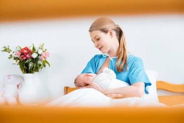 Selective focus of happy young mother breastfeeding newborn baby in hospital room stock vector