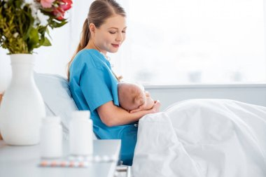 side view of happy young mother sitting on bed and breastfeeding newborn baby in hospital room
