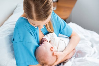 high angle view of young mother breastfeeding baby on bed in hospital room