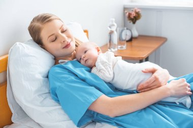 young mother sleeping on hospital bed with adorable baby lying on chest