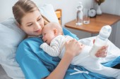 Fotografie high angle view of smiling young mother holding baby bottle with milk and lying in bed with adorable baby