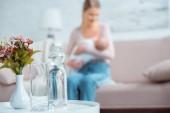 Fotografie Detailní pohled skla, láhev vody, květiny do vázy a matka kojení dítěte za doma