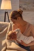 mladá matka sedí na pohovce a hospodářství novorozené dítě během kojení v noci